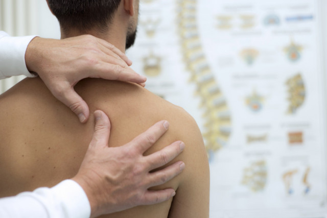 frozen shoulder symptoms | Doctor examining shoulder