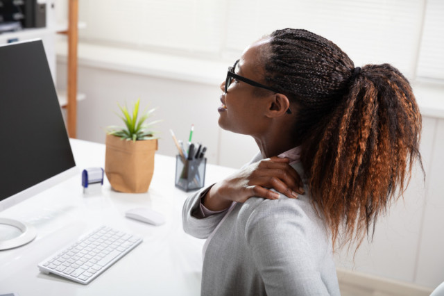 Woman sitting in front of computer with shoulder pain
