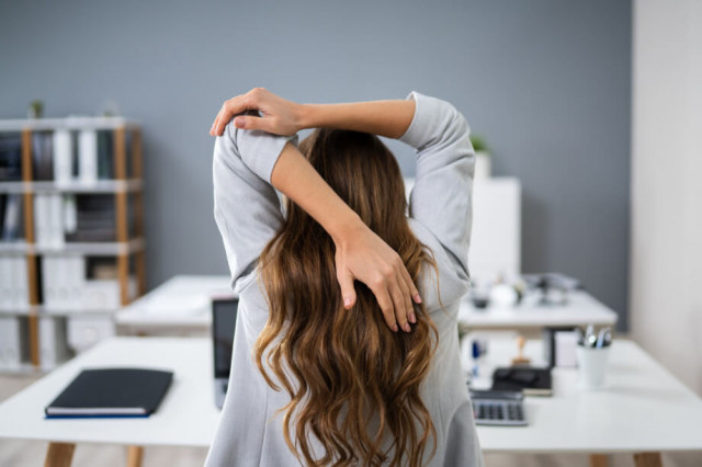 Woman sitting at a desk stretching | Stretching for Sore Shoulders
