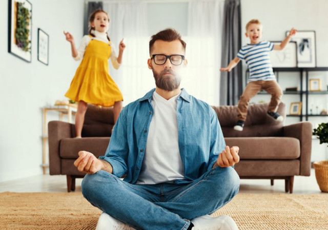 Man meditating and practicing yoga poses with children in the background